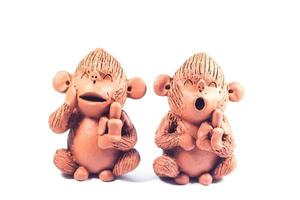 Two clay monkeys on a white background