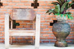 silla de madera cerca de una planta en maceta foto