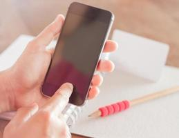 persona sosteniendo un teléfono inteligente en blanco