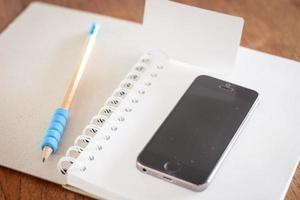 Business card and a phone on an open notebook
