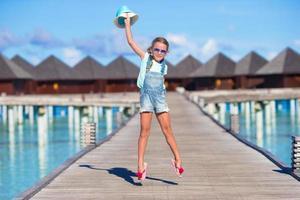 Maldivas, Asia del Sur, 2020 - Chica divirtiéndose en un embarcadero de madera cerca de bungalows acuáticos foto