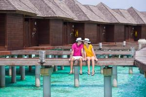Maldivas, Asia del Sur, 2020 - Pareja joven en un embarcadero de playa tropical cerca de un bungalow de agua foto