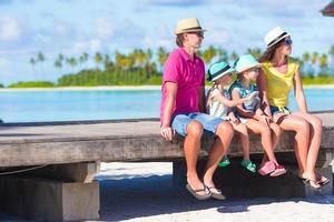 Familia de cuatro en el embarcadero de madera en Maldivas