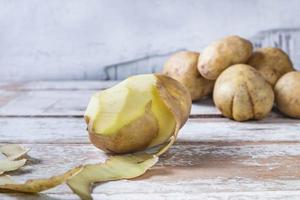 Potatoes are peeled on wooden background