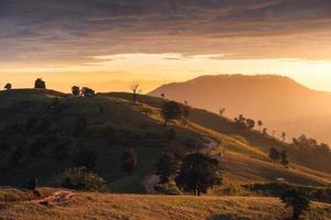 amanecer sobre las colinas y turistas acampando