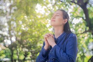 mujer rezando en un jardín