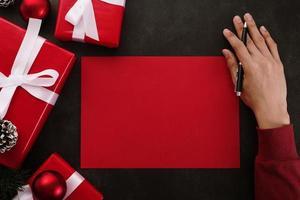 manos escribiendo maqueta de tarjeta de felicitación roja