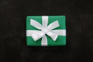 Top view of Christmas gift box wrapped with green paper