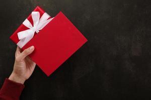 mano sosteniendo maqueta de tarjeta de felicitación roja