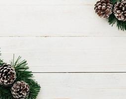 Decoración de cono de pino de Navidad sobre mesa de madera blanca