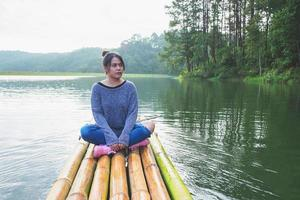 Woman sitting on a bamboo boat