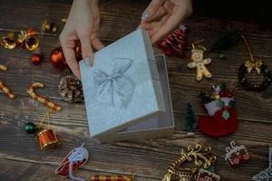 Manos con caja de regalo de navidad sobre un fondo de madera