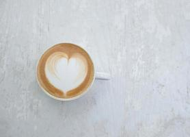 Cup of latte with heart shape on white table