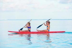 dos niñas, paddleboarding, en, un, playa tropical