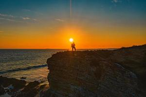 person standing on rock formation near sea during sunset