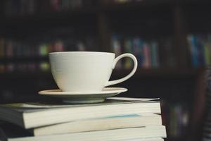 Coffee cup and stack of books on wood table