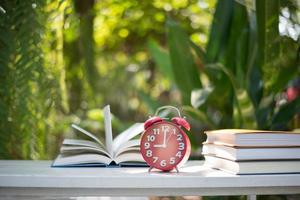 Red alarm clock with book on nature garden background
