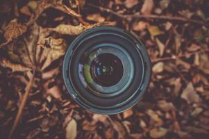 Black camera lens on brown dried leaves
