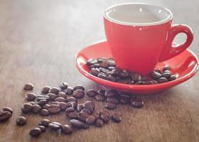 Close-up of a red coffee cup with coffee beans on a wooden table photo