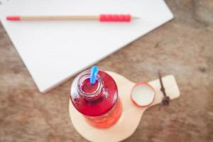 Red soda bottle on a wooden plate
