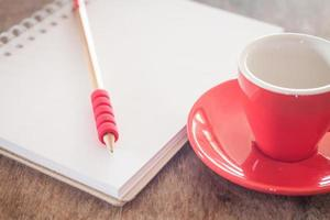 Red mug with a pencil and notebook