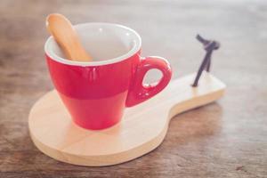 taza roja con una galleta y una bandeja de madera