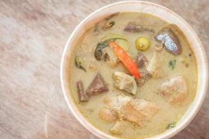 Top view of green curry in a wooden bowl