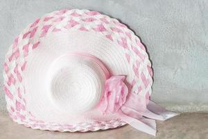 sombrero rosa con una cinta sobre un fondo gris