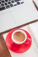 Vista superior de una taza de café roja con un bloc de notas y una computadora portátil