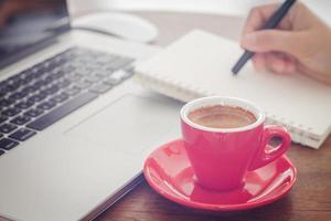 taza de café roja una persona escribiendo en un cuaderno foto