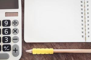 Close-up of a calculator and pencil with a notebook