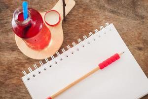 Bottle of red juice with a notebook