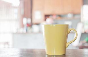 Yellow coffee mug in a cafe photo