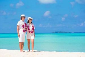 pareja en una playa vistiendo leis