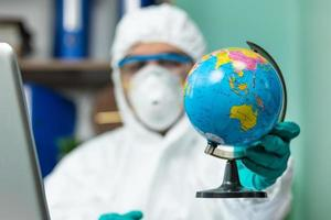 Person in protective suit holding earth globe with hand at office photo