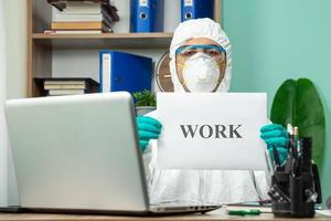 Person in protective suit holding work word at office