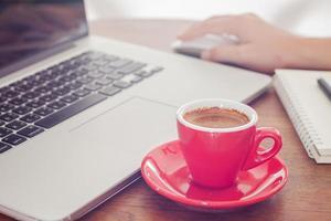 Taza de café roja con una persona que trabaja en una computadora portátil