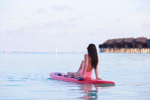 Maldivas, Asia del Sur, 2020 - Mujer en una tabla de surf en un resort foto