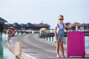 Maldivas, Asia del Sur, 2020 - Chica con equipaje en un muelle en un resort foto