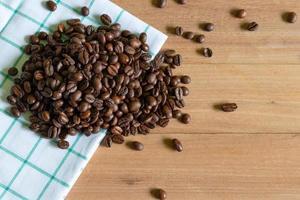Granos de café tostados sobre fondo de madera