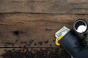 Money and coffee on wooden table, top view