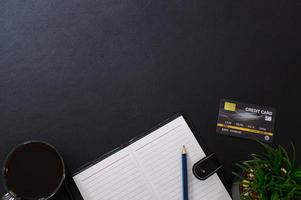 Notebook and credit card on black background