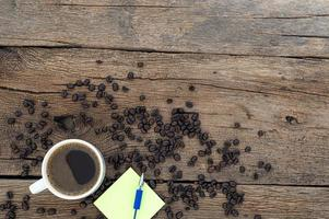 Note pad and coffee on wooden table, top view