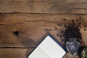 Wooden desk with coffee beans and notebook