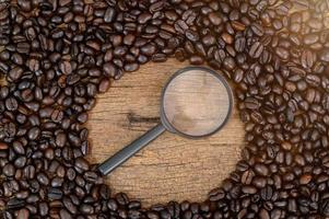 Wooden desk with coffee beans and magnifying glass