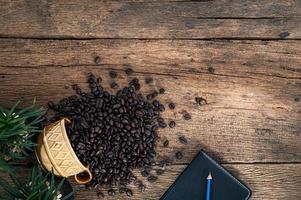 Wooden desk with notebook and coffee beans