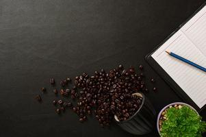 Black desk with notebook and coffee beans