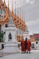 tres monjes caminando al lado del templo
