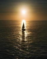 Sailboat on calm sea at golden hour photo