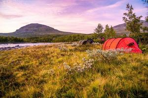 Red camping tent by a river